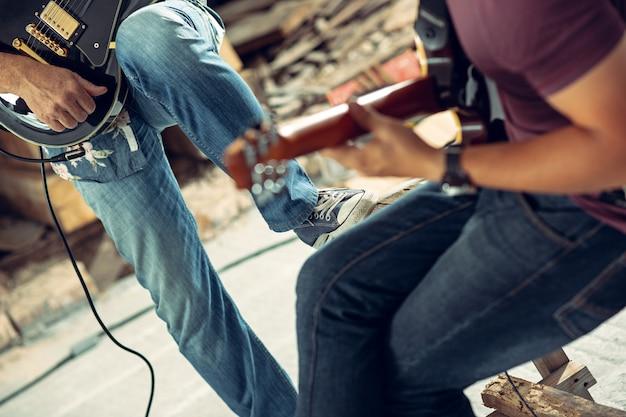 ロックミュージックバンドの繰り返し。エレクトリックギタープレーヤーとドラムセットの背後にあるドラマー。 無料写真