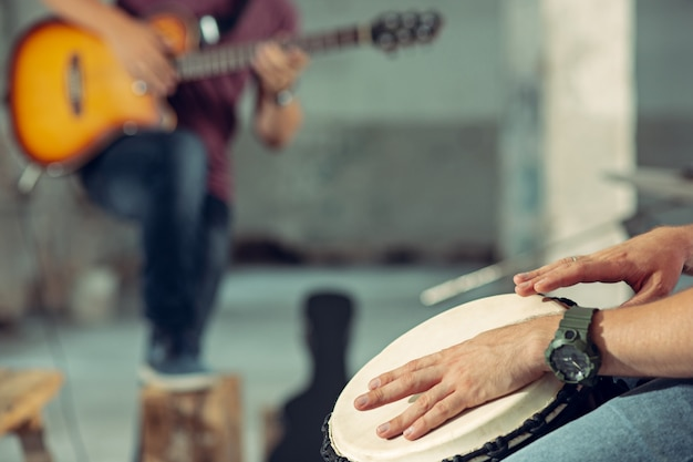 Repetition of rock music band. electric guitar player and drummer behind the drum set. Free Photo