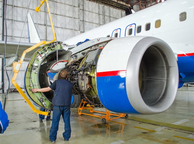 Replacing the engine on the plane, working people tap. concept maintenance of aircraft. Premium Photo
