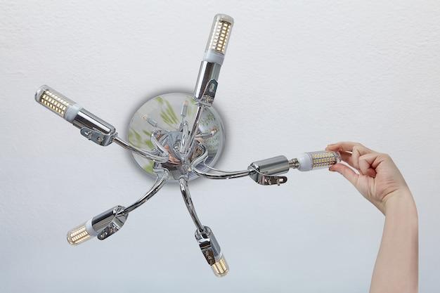 가정용 조명기구의 램프를 교체하는 여성 손은 램프 홀더에 Led 옥수수 조명을 설치합니다. 프리미엄 사진