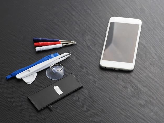 오래된 스마트 폰의 배터리 교체. 도구, 스마트 폰 및 배터리 나무 테이블에. 프리미엄 사진