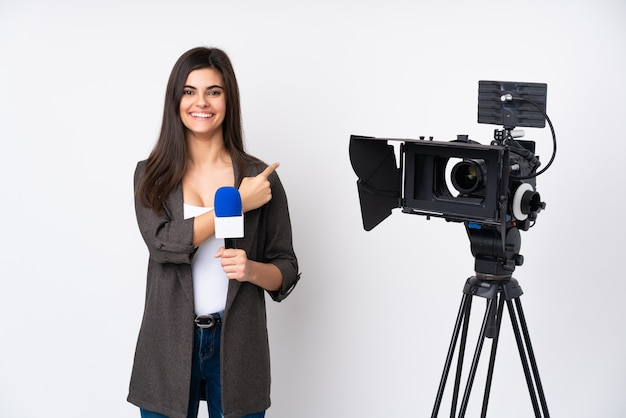 Reporter woman holding a microphone and reporting news over white wall pointing finger to the side Premium Photo