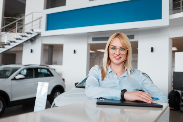 Representative of the car dealership is behind the reception Premium Photo