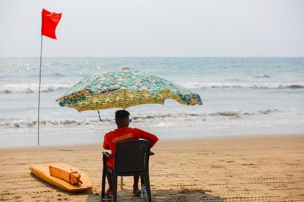 Rescuer of goa beach, watching the swimming and bathing in arambol goa, india Premium Photo