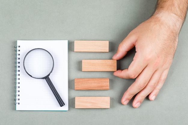 ノートブック、拡大鏡、灰色の背景の上面に木製のブロックの研究と検索結果の概念。結果の1つを手で選びます。横長画像 無料写真