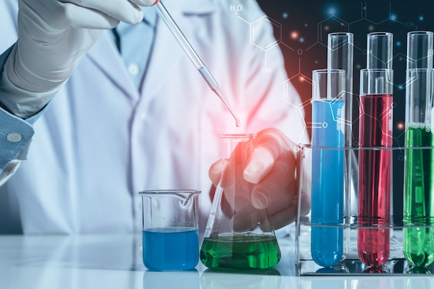 Researcher with glass laboratory chemical test tubes with liquid for analytical , medical, pharmaceutical and scientific research concept. Premium Photo