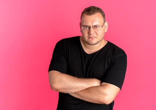 ピンクの上に腕を組んで眉をひそめている顔の黒いtシャツを着て眼鏡をかけている憤慨している太りすぎの男 無料写真
