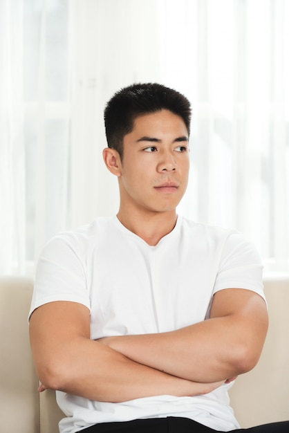 Resentful young asian man sitting on couch with crossed arms Free Photo