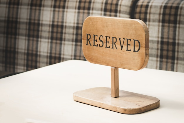 Reserved wooden sign on top of table in a restaurant Premium Photo