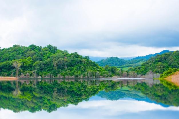 Водохранилище в долине с пасмурным небом и дождевыми облаками в таиланде Premium Фотографии