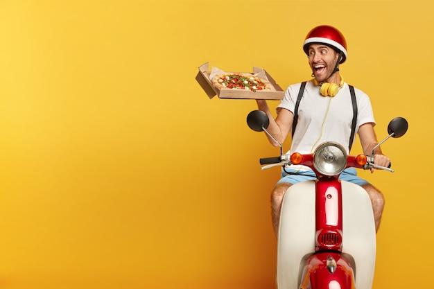 ピザを配達する赤いヘルメットとスクーターの責任あるハンサムな男性ドライバー 無料写真