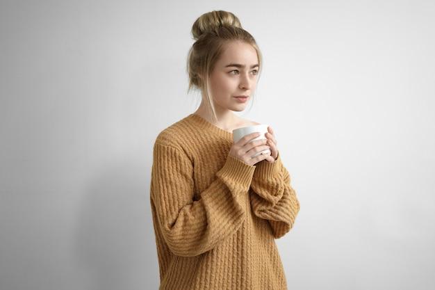 Концепция отдыха и релаксации. красивая молодая женщина в огромном пуловере с закрытыми глазами держит большую кружку обеими руками, пьет горячее какао или кофе в помещении, радостно улыбается Бесплатные Фотографии