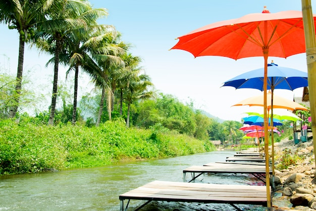 Restaurant by the river and decorated with colorful umbrella. thailand. Premium Photo