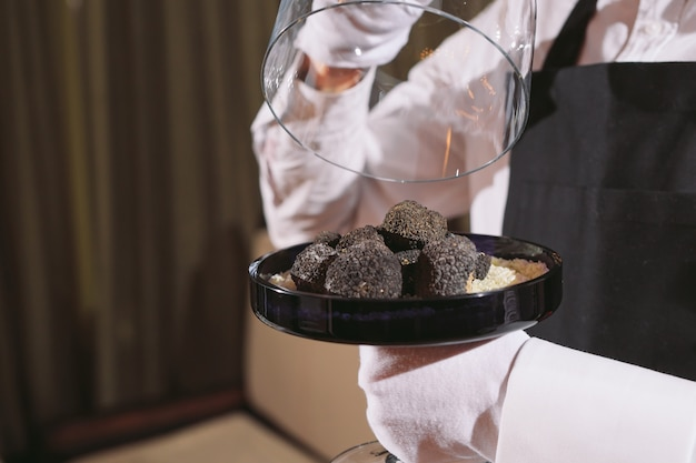 Restaurant chef delicacy. truffle vegan food mushroom. waiter service meal concept Premium Photo