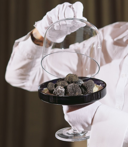 Restaurant chef delicacy. truffle vegan food mushroom. waiter service meal concept Premium Photo