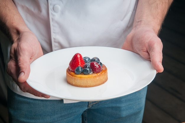 Restaurant chef holding plate with sweet dessert Free Photo