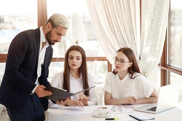 Il direttore del ristorante sta mostrando schemi finanziari nei documenti e due assistenti che le donne ascoltano con attenzione Foto Gratuite