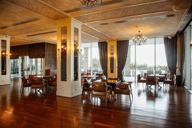 Restaurant hall with leather armchairs and french windows Free Photo