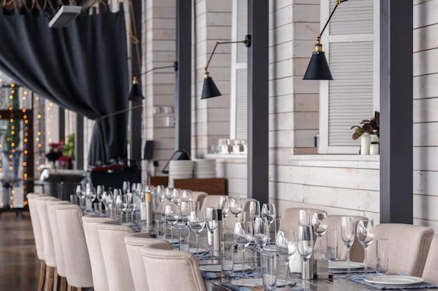 ヴィンテージグレーの木製テーブルの上の行に立つレストランのインテリア、サービングワインと水のグラス、プレート、フォーク、ナイフ、テキスタイルナプキンに Premium写真