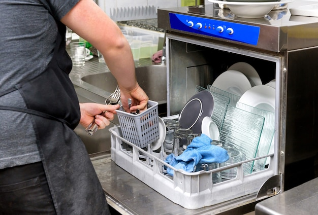 Restaurant kitchen worker emptying a dishwasher removing clean cutlery from the basket in a close up on his hands Premium Photo