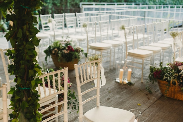 A restaurant prepares a wooden platform to place vintage chairs and create a retro atmosphere for a wedding ceremony. Premium Photo