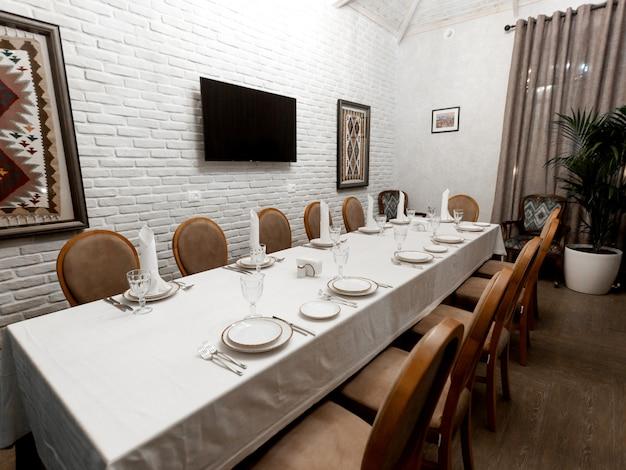 Ristorante sala privata con pareti in pietra bianca e sedie marroni Foto Gratuite