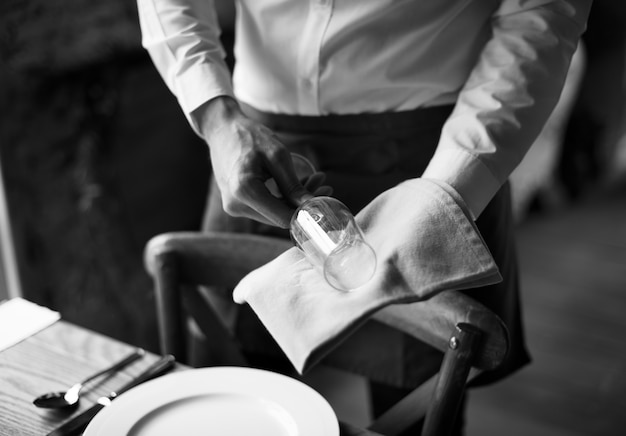 Restaurant staff wiping glass on table setting service for reception Premium Photo