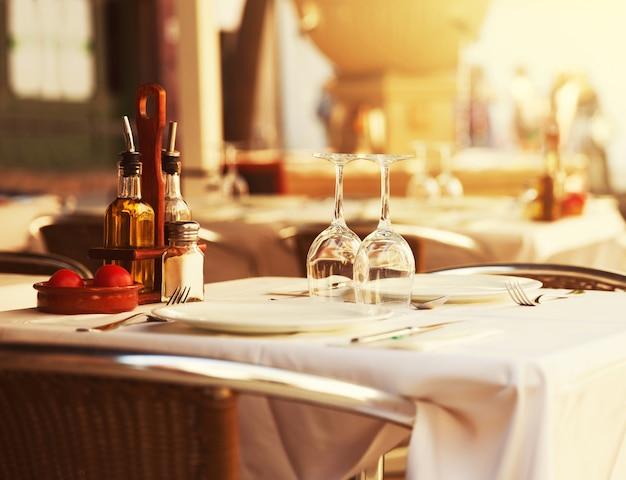 Столик в ресторане на закате Premium Фотографии