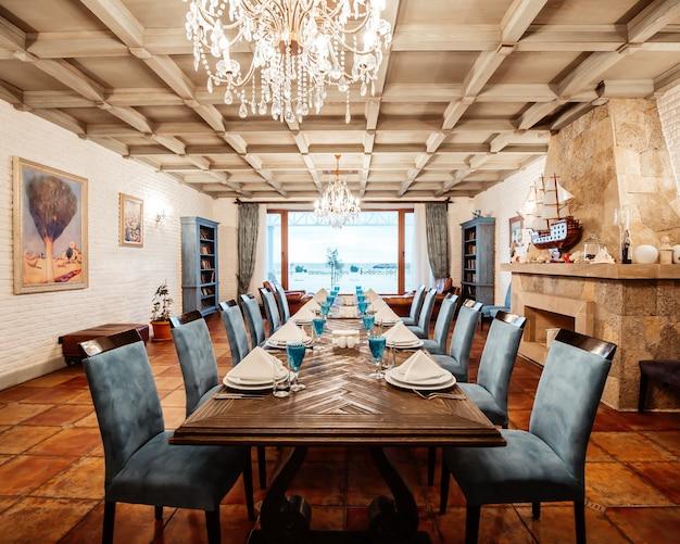 青い椅子、暖炉、白いレンガの壁、広い窓がある12人用のレストランテーブル 無料写真