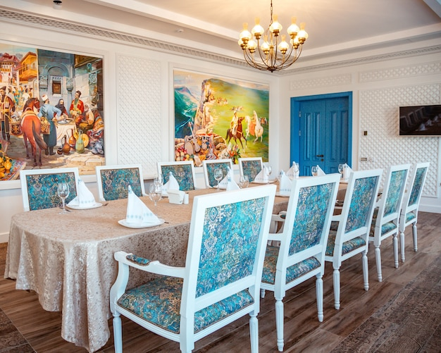 Restaurant table with classic white chairs and turquoise fabric Free Photo