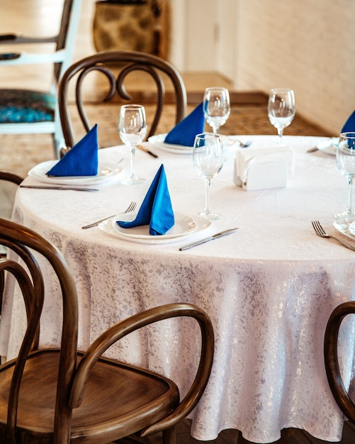 Restaurant table with white lace table cloth and blue napkins Free Photo