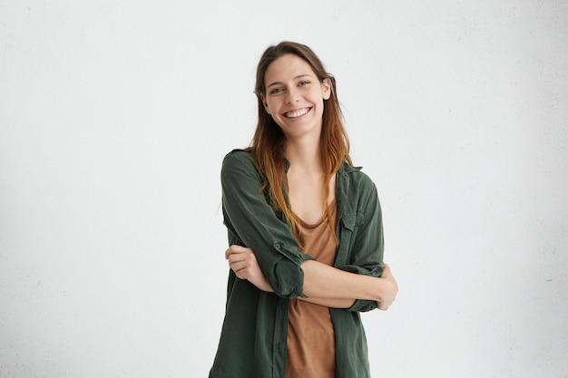 彼女の完璧な歯のポーズを示す誠実で楽しい笑顔を持っている交差した手を染めた髪立って安らかな女性 無料写真