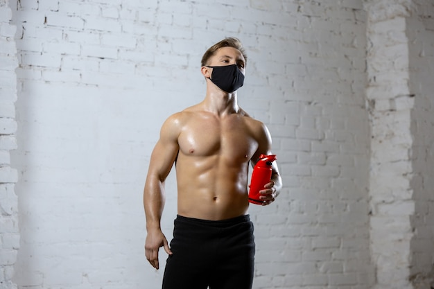 Resting. professional athletes training on brick wall wearing face masks. sport during quarantine of coronavirus worldwide pandemic. young couple practicing in gym safe using equipment. Free Photo