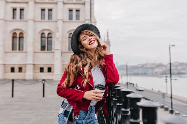 Отдыхающая женщина в модной шляпе позирует с закрытыми глазами на размытой уличной стене и пьет латте Бесплатные Фотографии