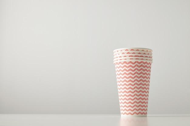 白いテーブルで隔離の赤い線のパターンで飾られた4つの紙コップの小売セット 無料写真