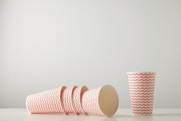 赤い線のパターンで飾られた3つの紙コップの小売セットは落ち着き、白いテーブルの上に孤立して近くに立っています 無料写真