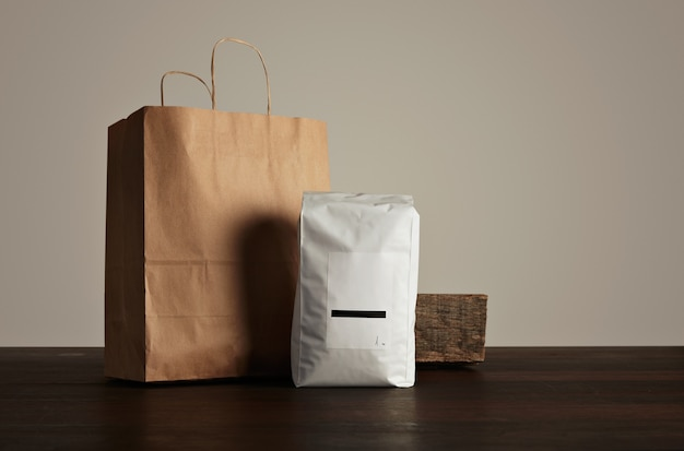 Retailer merchandise pack: big hermetic pouch white with blank label presented near of craft paper bag and rustic wooden brick on red table Free Photo