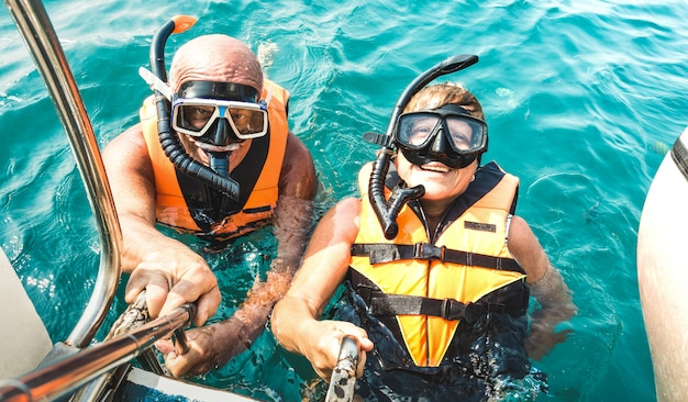 Retired couple taking happy selfie in tropical sea excursion with life vests and snorkel masks Premium Photo
