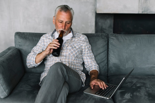Retired man drinking beer from bottle using laptop Free Photo