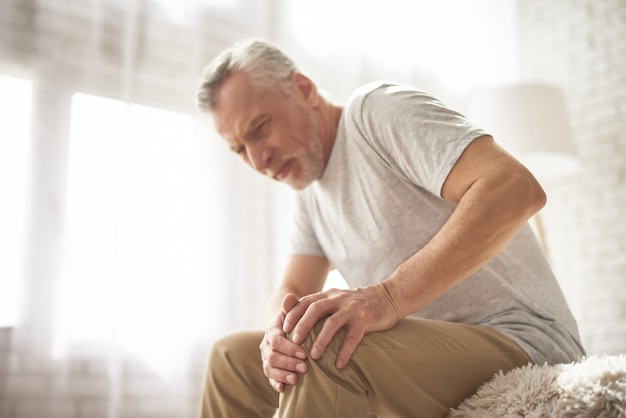 Retired man pensioner suffering knee pain at home. Premium Photo