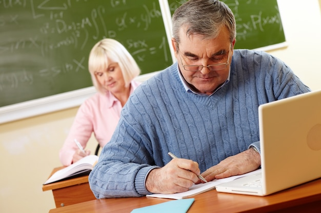 Retired man with glasses doing homework Free Photo