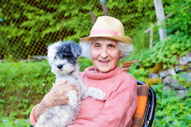 Donna pensionata seduta con il suo cane Foto Gratuite