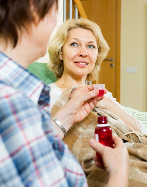 Retirement home employee offering  mixture to  patient Free Photo