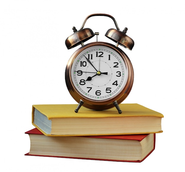 Retro alarm clock and books isolated on white . Premium Photo