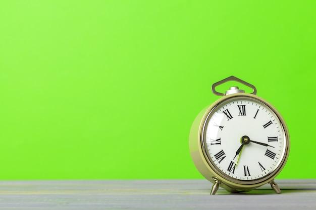 Retro alarm clock on green wall background Premium Photo