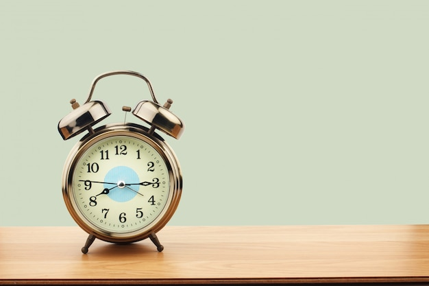 Retro alarm clock on old wooden table on green wall background Premium Photo