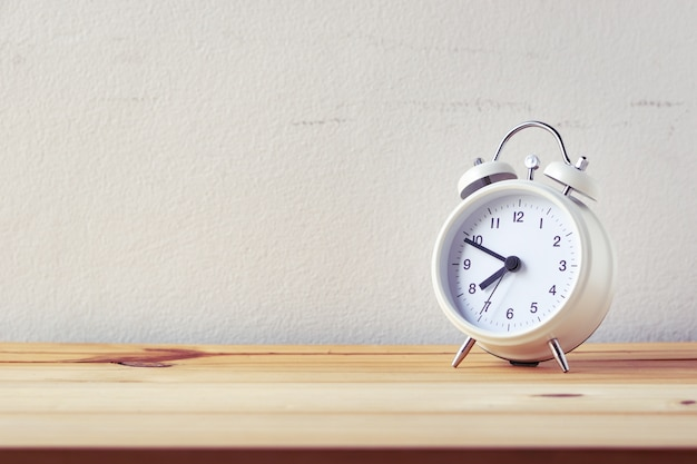 Retro alarm clock on wood table Premium Photo