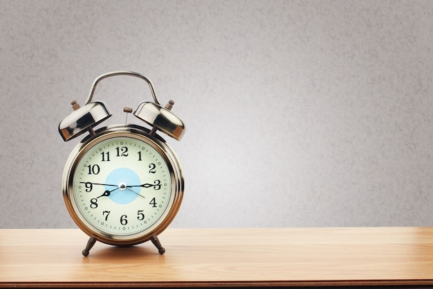 Retro alarm clock on wooden table with purple wall background Premium Photo