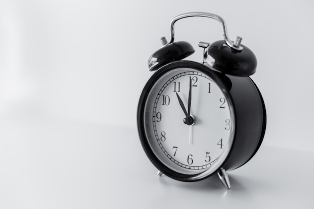 Retro black bell clock on white room background with space for text Premium Photo