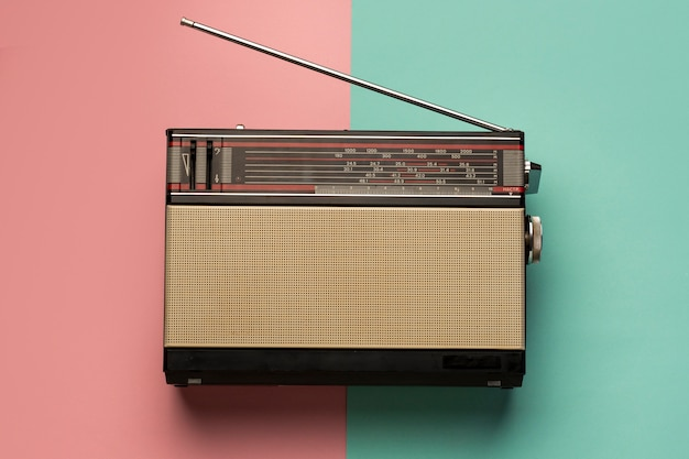 Retro broadcast radio receiver on pink and light blue background Free Photo